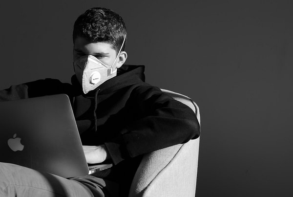 Man wearing mask looking at laptop